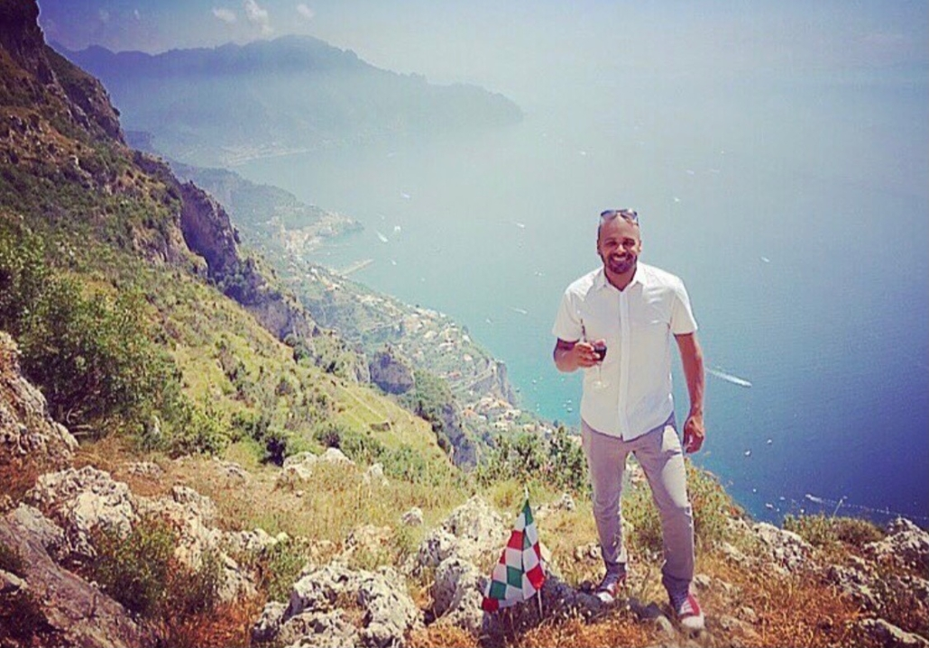 Jason Humble standing on mountainside with ocean in backround